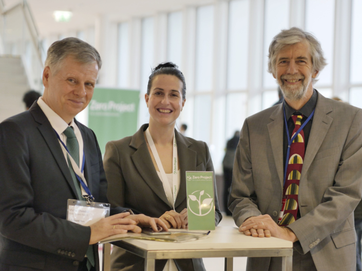 Michael Fembek, Helena Guggenbichler and Max Rubisch stand at a high table in the exhibition area facing the camera