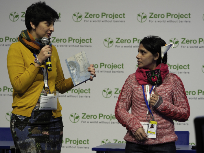 Roxana Damaschin-Tecu and Elisabeta Moldovan stand in front of a Zero Project backdrop. Roxana stands on the left, speaking and holding a microphone and a book. Elisabeta on the left holds a ceramic flower.