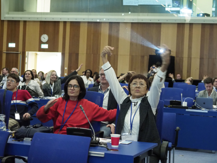 Conference participants sitting in their chairs make movements with their arms