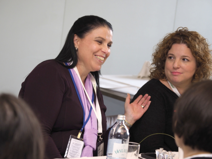 Two women sit next to each other at a table. The women on the left is smiling and talking and the womeon on the right is listening to her.