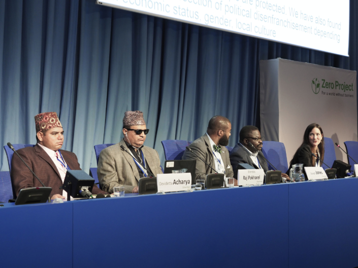 Devidetta Achyara, Birendra Raj Pokharel, Joseph Jones, Action Amos and Tracy Vaughan Gough sit on stage in the main conference room with microphones in front of them