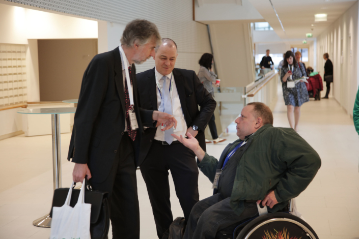 Three men talking in the corridor outside of the conference rooms. One of the men is in a wheelchair.
