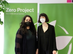 Two young woman wearing black and standing in front of the green Zero Project banner
